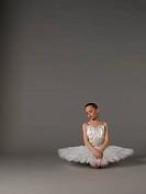 Girl in white tutu kneeling.