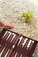 Backgammon Board cropped and Bowl with Grapes laying on a Carpet