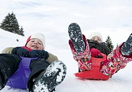 Two children tobogganing