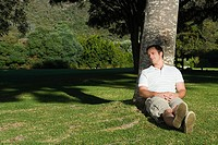 Man resting against tree