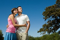 Couple standing in park with arms around each other
