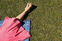 Legs of woman relaxing on picnic blanket