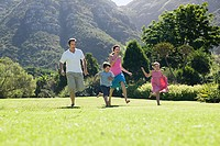 Family running along grass in a park