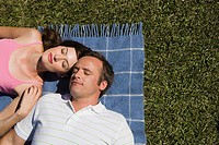 Couple resting on picnic blanket