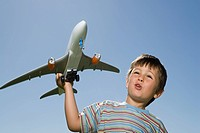 Little boy playing with toy aeroplane