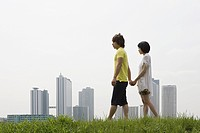 Young couple walking by city skyline