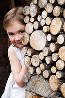 Girl hiding behind logs.