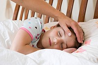 Sleeping girl with adult hand on her head
