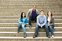 Four young friends sitting on steps