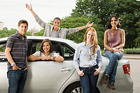Five young friends around a car
