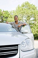 Smiling young man with his car