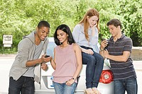 Four young friends using cellular telephones