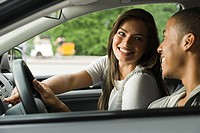 Smiling young couple in a car