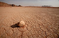 Single stone lying on parched desert floor, Wadi Rum, Jordan
