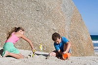Girl and boy making sandcastles by large rock at the beach