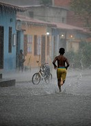Local boy running over street during heavy cloudburst, Chuao, Venezuela