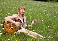 woman playing guitar in meadow