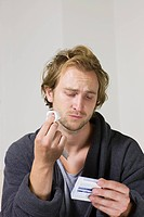 Man looking at packet of tablets