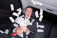 Businessman in car with bank notes