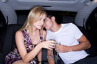 Couple drinking champagne in the back of a car