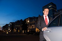 Businessman standing by a car