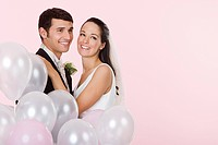 Bride and groom with a bunch of balloons
