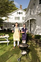 Couple standing by barbecue