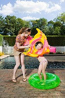 Mother and daughter playing by swimming pool
