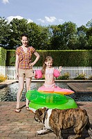 Mother and daughter with dog by swimming pool