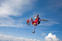 football player doing parachute jumping, full shot