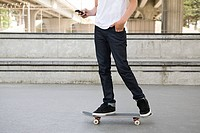Teenage boy on skateboard with cellphone