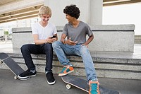 Teenage boys with skateboards and cellphone