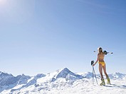 woman in bikini on mountain with skis