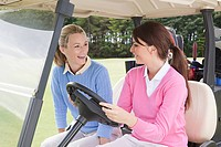 Female friends driving a golf cart (thumbnail)