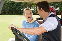 Couple driving a golf cart