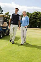 Couple walking on golf fairway