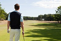Rear view of a male golfer on the fairway