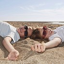 Children with sunglasses laying on sand