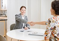 Businesswoman shaking hands with woman in dining room