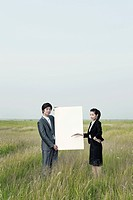 business woman and man holding a notice board, outside