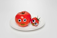 cherry tomatos and tomato with face on plate, close_up