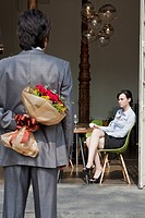 Business couple in office, man holding roses behind back