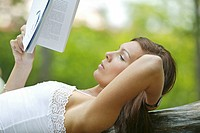 young woman relaxing outdoors reading a book