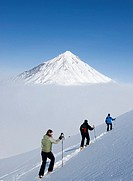 Three montaineering skiers on Mountain in Kamchatka Russia with Koryaksky volcano in distance 2008