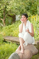 woman sitting in garden drinkin water