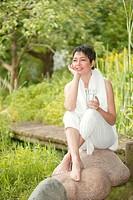 woman sitting in garden drinkin water