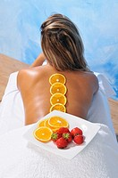 Dish with oranges and strawberries in the back of a young woman for a natural beauty treatment