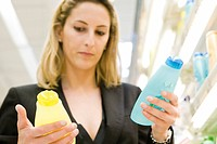 Woman comparing body care products (thumbnail)