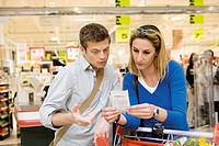 Couple reviewing sales receipt in store