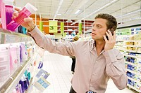 Man using cell phone, selecting bottle of shower gel from supermarket shelf
